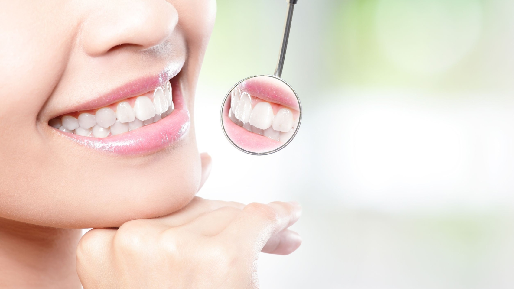20481718 - healthy woman teeth and a dentist mouth mirror with nature green background